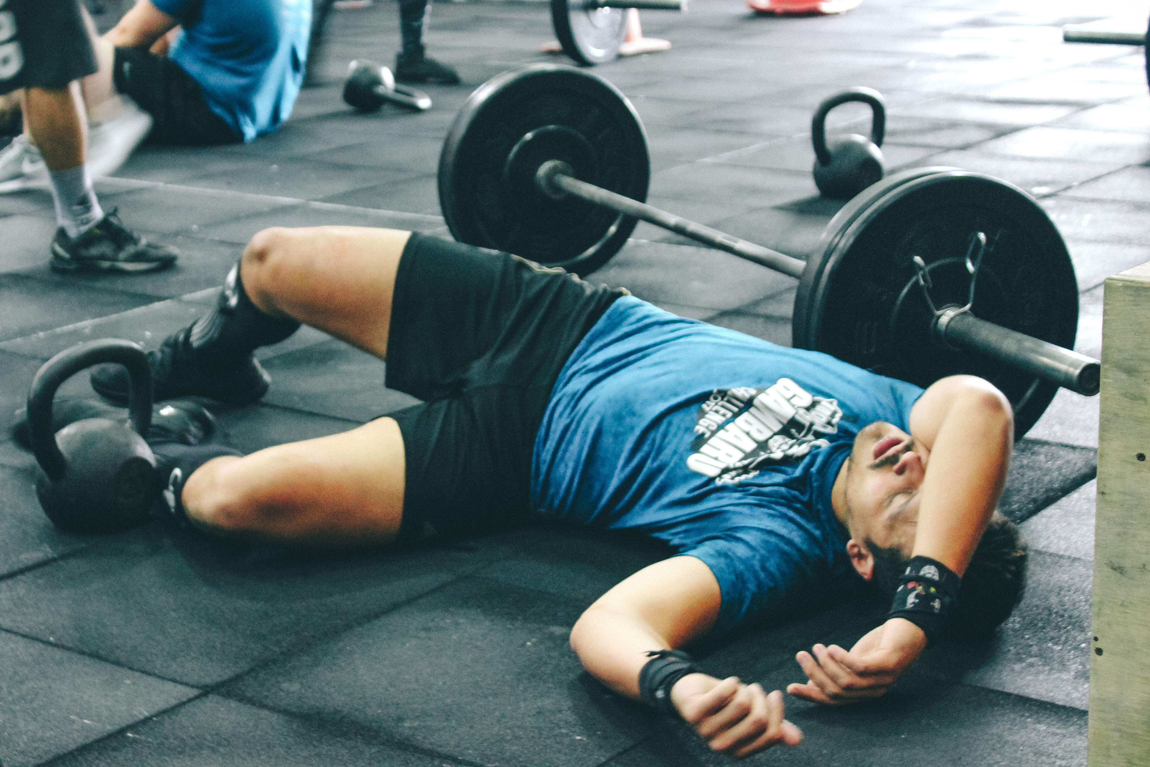 Canva - Man Lying on Rubber Mat Near Barbell Inside the Gym